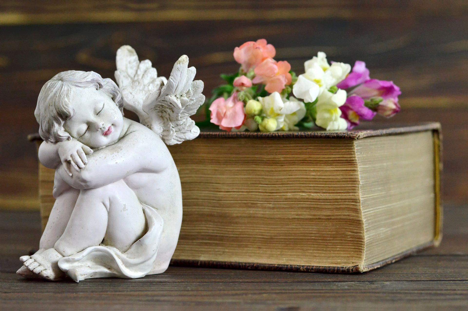Angel, flowers and old book on wooden background
